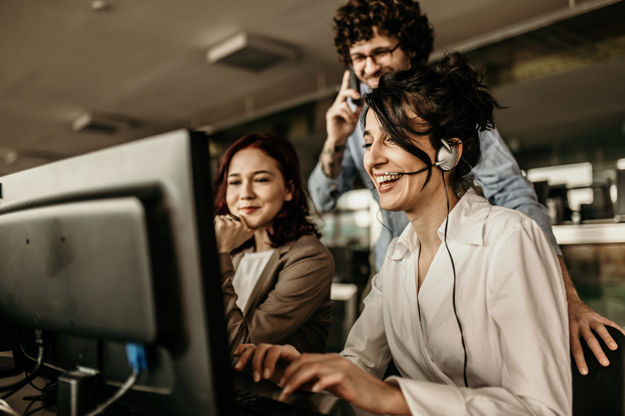 Happy sales representatives in an office working on computers to speak with customers.