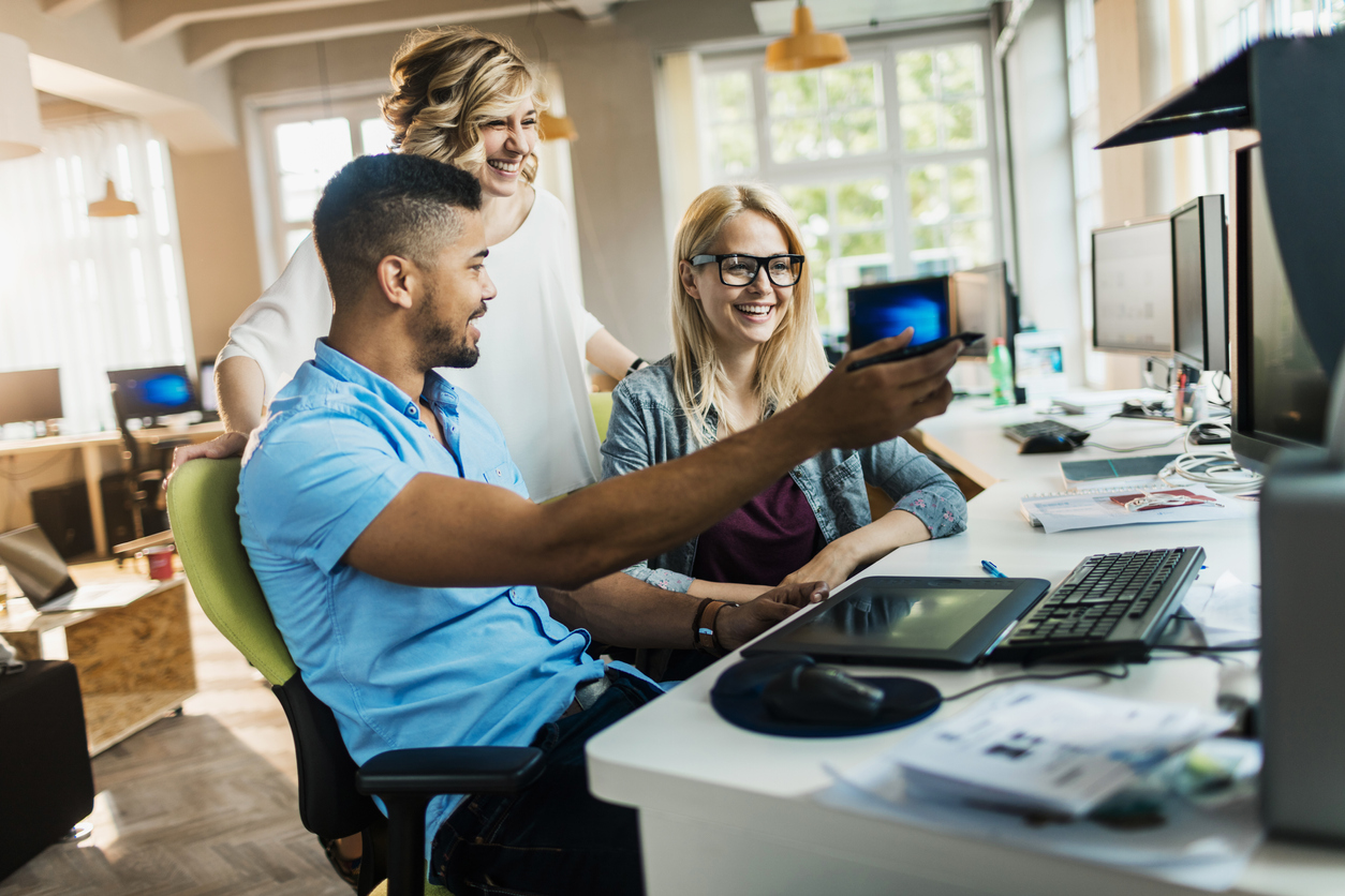 Team of diverse employees using computers while discussing CRM systems in an office.