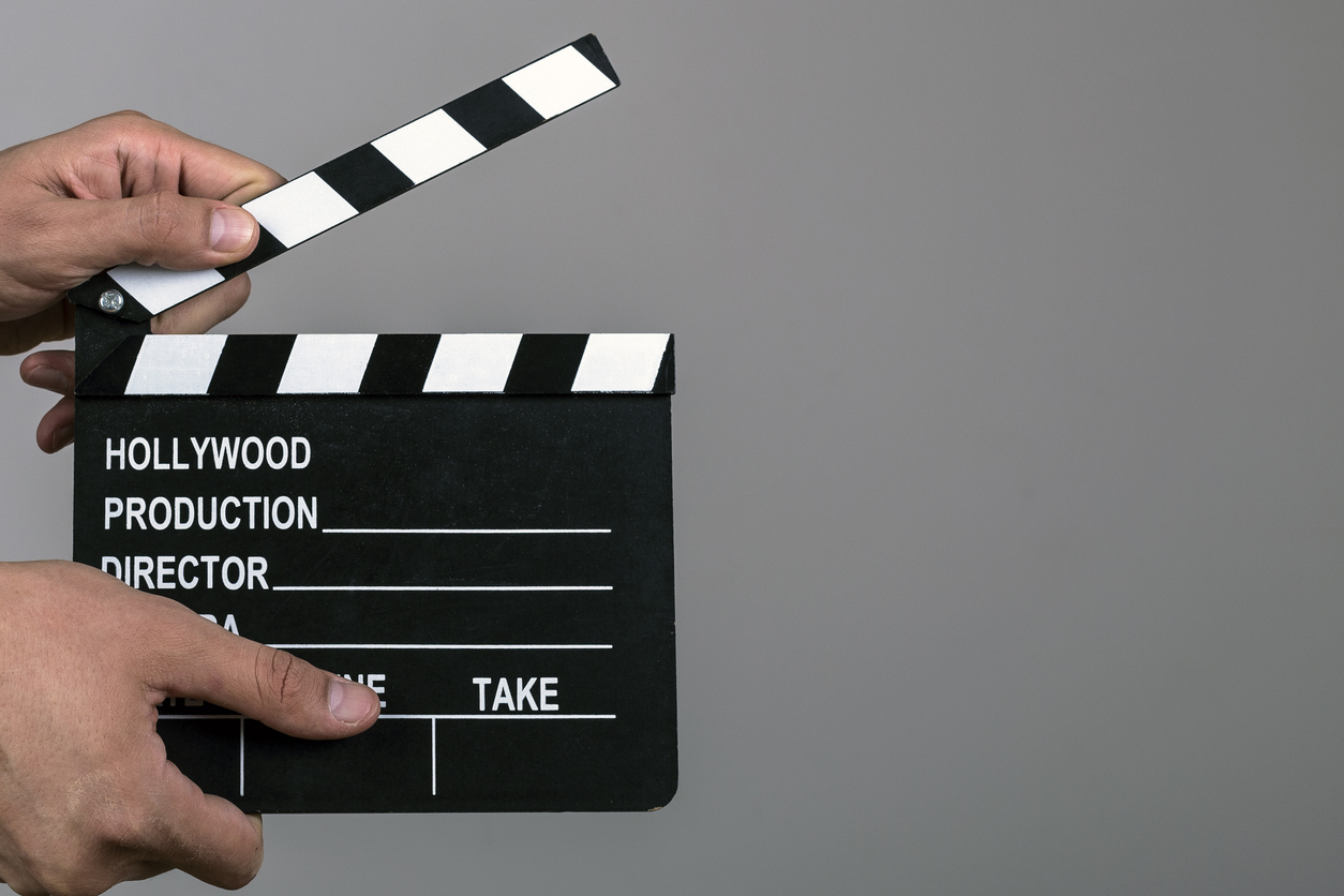 cropped image of a hand holding a black clapboard