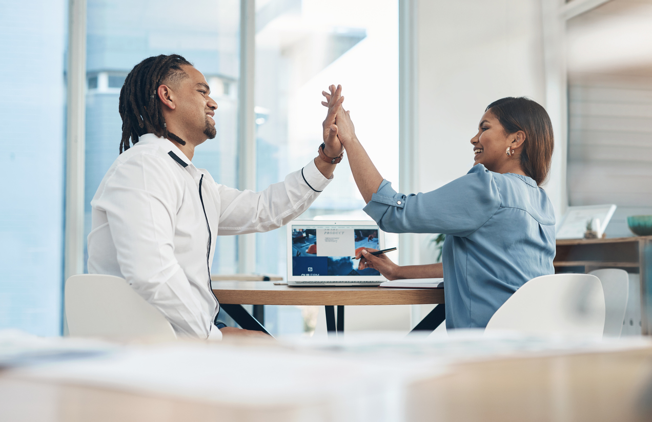 Two sales professionals in an office giving a high five to each other to celebrate business accomplishments.