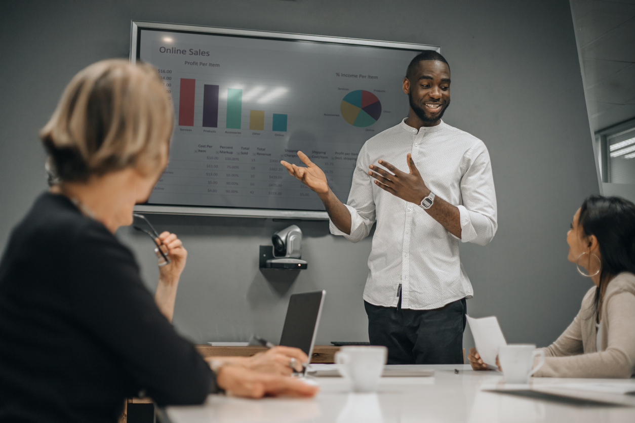 Male sales professional giving a sales presentation to his colleagues in a conference room.