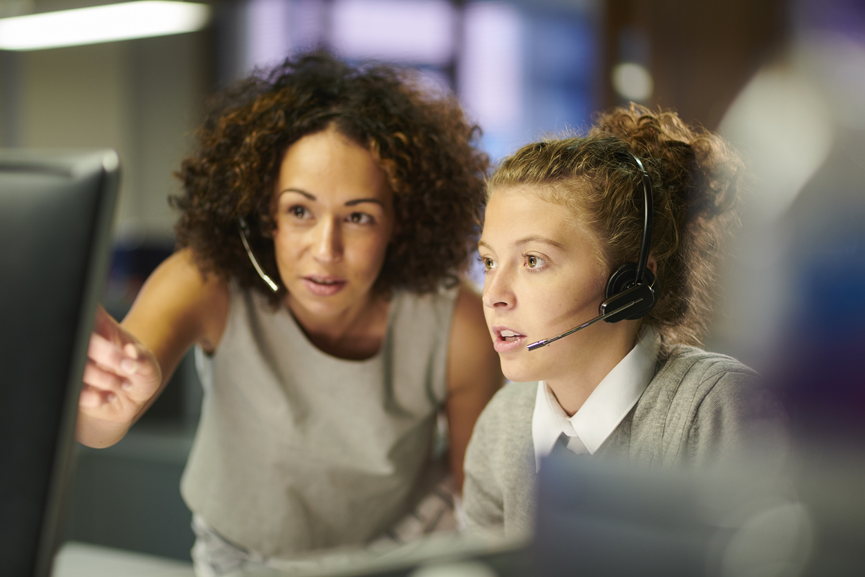 Businesswoman and female employee wearing headsets while managing their CRM sales process automation.