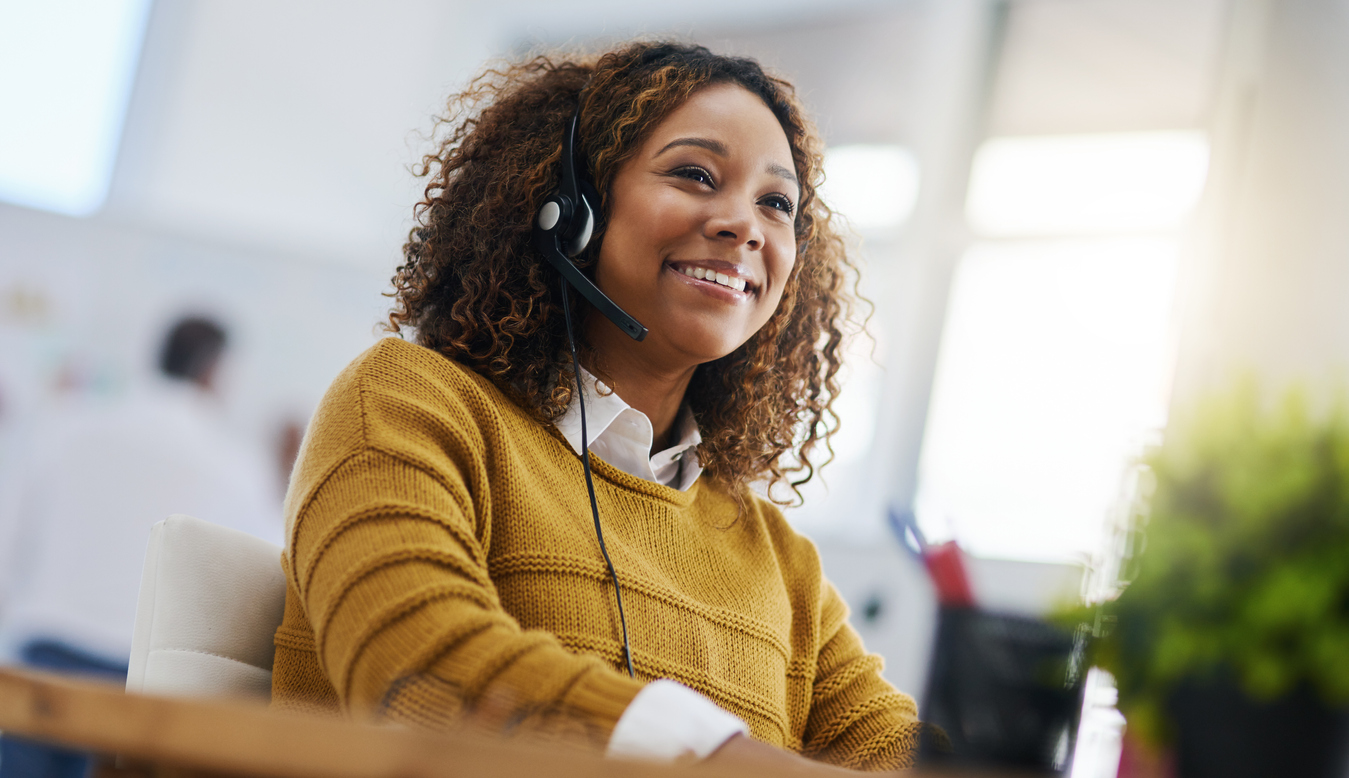 Female employee wearing a headset while using a CRM system to interact with company clients.