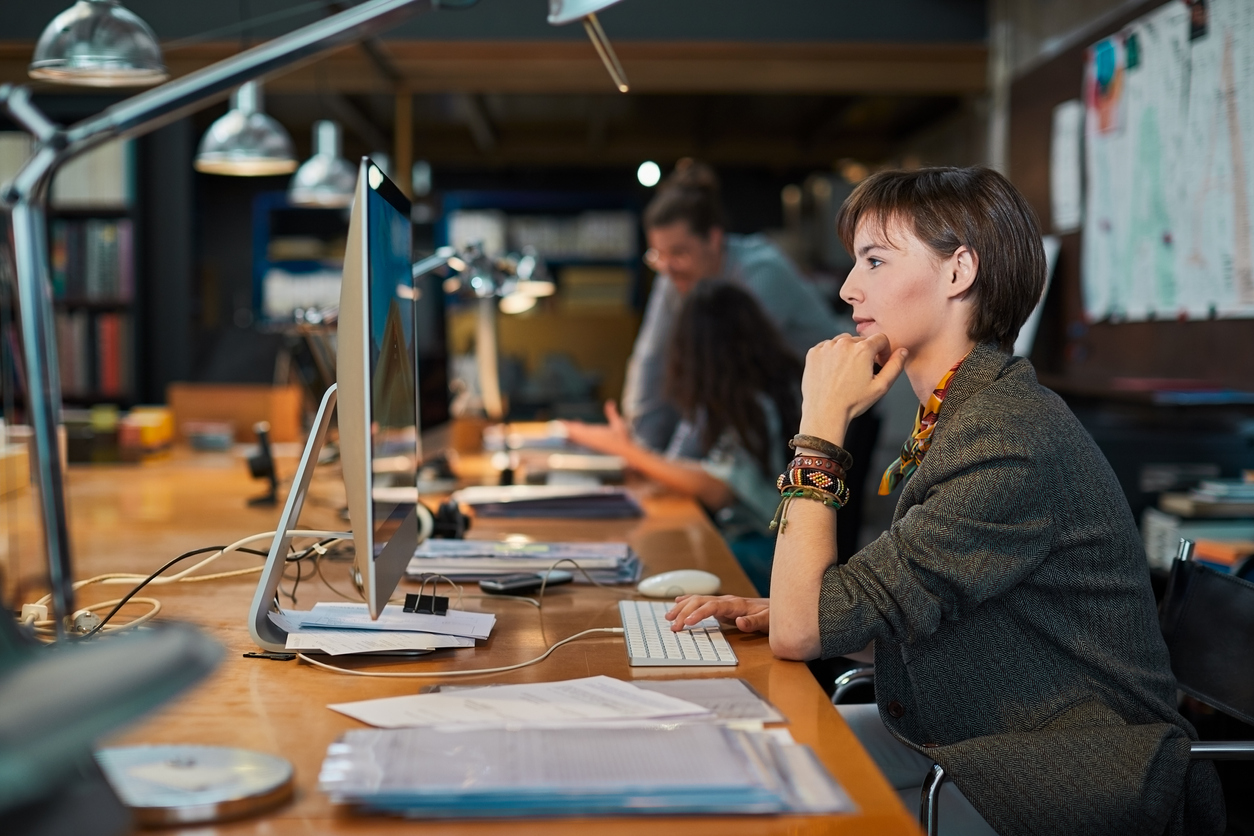 Female professional in an office using a computer to access their company CRM.